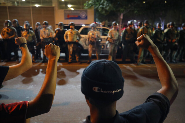 Protesters raise their fists during a rally Monday, June 1, 2020, in Las Vegas, over the death of George Floyd, a black man who was in police custody in Minneapolis. (AP Photo/John Locher)