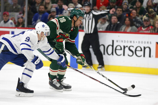 Minnesota Wild left wing Jordan Greenway (18) controls the puck in front of Toronto Maple Leafs center Jason Spezza (19) and Maple Leafs center Auston Matthews (34) in the first period of an NHL hockey game Tuesday, Dec. 31, 2019, in St. Paul, Minn. (AP Photo/Andy Clayton-King)