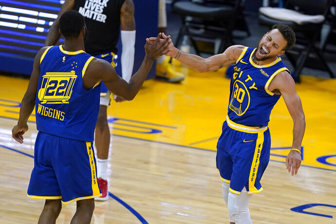Golden State Warriors forward Andrew Wiggins (22) celebrates with guard Stephen Curry (30) after Wiggins made a 3-point shot against the Los Angeles Clippers during the second half of an NBA basketball game in San Francisco, Friday, Jan. 8, 2021. (AP Photo/Tony Avelar)