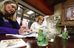 Jo Trizila, left, President and CEO of Trizcom Public Relations, conducts a meeting as Ann Littmann sits by at Trizila's offices in Dallas, Tuesday, Jan. 21, 2020. The recent flu outbreak can really impact small businesses with small staffs and hurt a company's productivity. Some owners, like Trizila, are trying to mitigate the damage so the flu will not become a nightmare when they're trying to get clients' work done. (AP Photo/LM Otero)