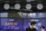 Currency traders walk by the screens showing the Korea Composite Stock Price Index (KOSPI), left, and the foreign exchange rate between U.S. dollar and South Korean won at the foreign exchange dealing room in Seoul, South Korea, Friday, Jan. 29, 2021. Asian stock markets were mixed Friday after Wall Street rebounded from its biggest loss in nearly three months, while Japan reported December factory output weakened. (AP Photo/Lee Jin-man)