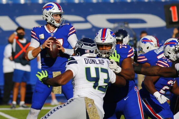 Buffalo Bills quarterback Josh Allen, left, looks to pass as teammate offensive tackle Daryl Williams (75) blocks Seattle Seahawks Carlos Dunlap (43) during the first half of an NFL football game Sunday, Nov. 8, 2020, in Orchard Park, N.Y. (AP Photo/Jeffrey T. Barnes)