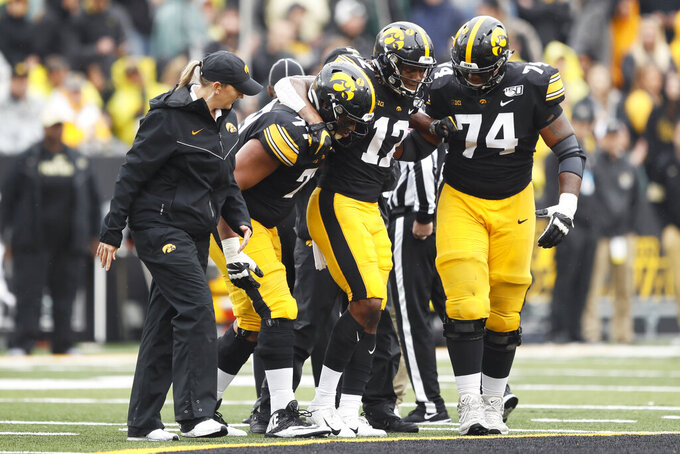 Iowa wide receiver Brandon Smith (12) is helped off the field by teammates Alaric Jackson (77) and Tristan Wirfs (74) after getting injured during the second half of an NCAA college football game against Purdue, Saturday, Oct. 19, 2019, in Iowa City, Iowa. Iowa won 26-20. (AP Photo/Charlie Neibergall)