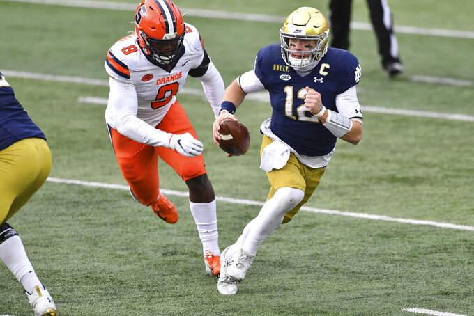 Notre Dame quarterback Ian Book (12) runs as Syracuse defensive lineman Jonathan Kingsley (9) pursues in the first half of an NCAA college football game Saturday, Dec. 5, 2020, in South Bend, Ind. (Matt Cashore/Pool Photo via AP)