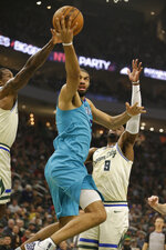 Charlotte Hornets' Nicolas Batum, center, shoots against the Milwaukee Bucks' Giannis Antetokounmpo during the first half of an NBA basketball game Saturday, Nov. 30, 2019, in Milwaukee. (AP Photo/Jeffrey Phelps)