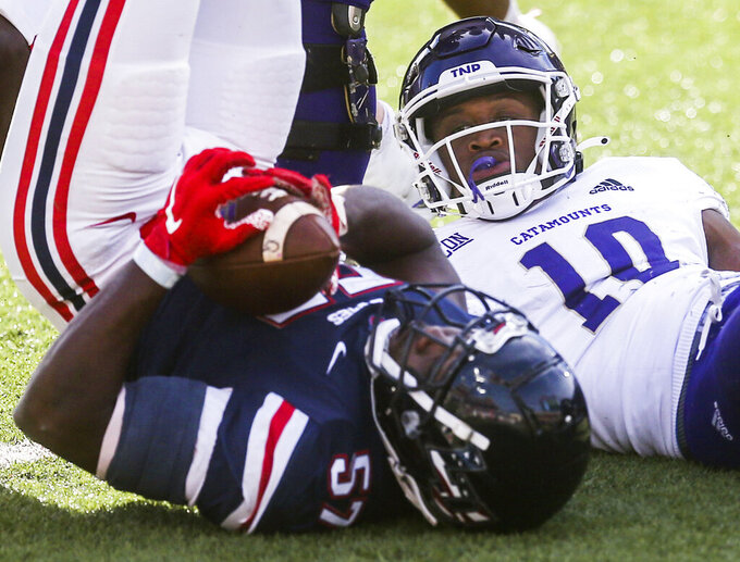 Liberty linebacker Carl Poole (57) swoops up the ball after he forced Western Carolina running back Malik Richardson (10) to fumble during the second half of an NCAA football game Saturday, Nov. 14, 2020, in Lynchburg, Va. (AP Photo/Shaban Athuman)