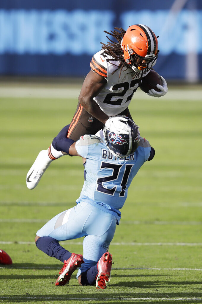 Cleveland Browns running back Kareem Hunt (27) hits Tennessee Titans cornerback Malcolm Butler (21) in the second half of an NFL football game Sunday, Dec. 6, 2020, in Nashville, Tenn. (AP Photo/Ben Margot)
