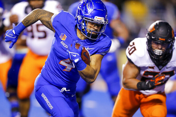 Boise State running back Cyrus Habibi-Likio (4) turns the corner against Oklahoma State linebacker Malcolm Rodriguez (20) for a 5-yard touchdown run during the first half of an NCAA college football game Saturday, Sept. 18, 2021, in Boise, Idaho. (AP Photo/Steve Conner)