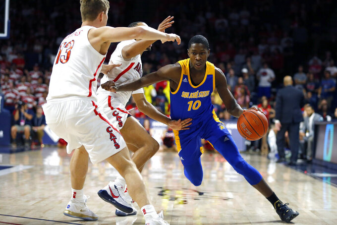 San Jose State guard Omari Moore (10) drives on Arizona's Jemarl Baker Jr. and Stone Gettings (13) during the first half of an NCAA college basketball game Thursday, Nov. 14, 2019, in Tucson, Ariz. (AP Photo/Rick Scuteri)