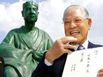FILE - In this May 31, 2007, file photo, former Taiwanese President Lee Teng-hui smiles as he holds his own Haiku poem in front of a statue of Basho Matsuo, popular Haiku poet at Basho Museum in Tokyo. Local media are reporting that ex-Taiwanese President Lee Teng-hui, who oversaw the island's transition to full democracy, has died. Lee was 97 and had largely dropped out of public life in his later years. (AP Photo/Koji Sasahara, File)