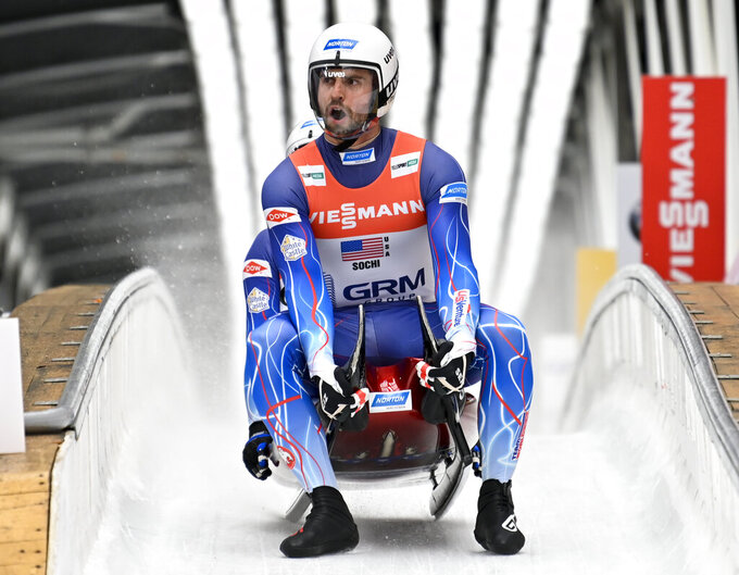 FILE - Chris Mazdzer, front, and Jayson Terdiman of the United States finish their team relay race at the World Luge Championships in Krasnaya Polyana, near the Black Sea resort of Sochi, southern Russia, in this Sunday, Feb. 16, 2020, file photo. Reigning Olympic luge silver medalist Chris Mazdzer of the U.S. said Thursday, Sept. 30, 2021, that he broke his right foot during a preseason training run, and will need some time before figuring out a new plan to get ready for this winter's Beijing Games.  (AP Photo/Artur Lebedev, File)