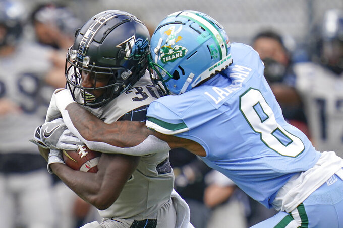 Central Florida running back Greg McCrae, left, is tackled by Tulane cornerback Willie Langham (8) after a gain during the first half of an NCAA college football game, Saturday, Oct. 24, 2020, in Orlando, Fla. (AP Photo/John Raoux)