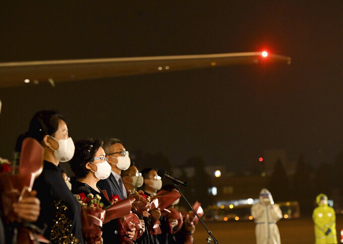In this photo released by China's Xinhua News Agency, staff members from the Chinese Consulate in Houston, USA, arrive at an airport in Beijing, Monday, Aug. 17, 2020. A charter flight carrying employees of the consulate, which was ordered closed by the U.S. government in July amid escalating diplomatic tensions, arrived in Beijing on Monday night. (Yue Yuewei/Xinhua via AP)