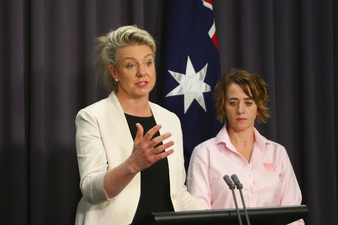 Australian Agriculture Minister Bridget McKenzie, left, and pork industry executive Margo Andrae address the media at Parliament House in Canberra, Australia Tuesday, Oct. 15, 2019, on the threat of African swine fever. Australia for the first time has canceled a tourist's visa over undeclared food as the country tries to keep itself free of the disease. (AP Photo/Rod McGuirk)
