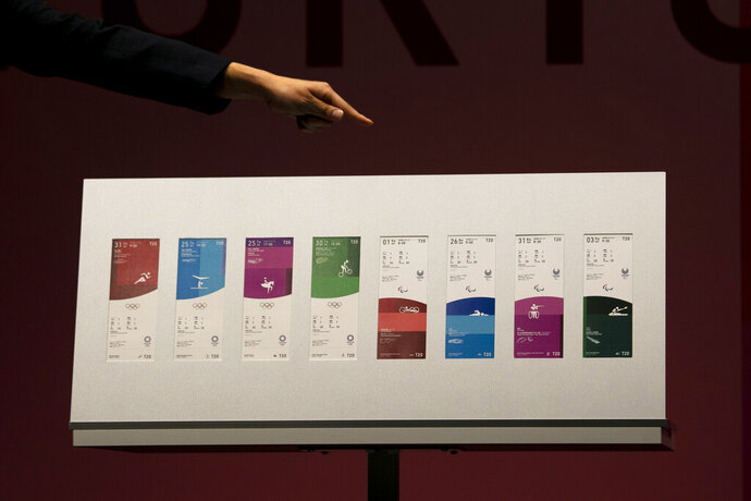 Japanese comedian Ryota Yamasato points to tickets for the Tokyo 2020 Olympics and Paralympics Wednesday, Jan. 15, 2020, in Tokyo. (AP Photo/Jae C. Hong)