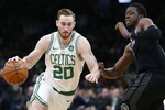 Boston Celtics' Gordon Hayward, left, drives past Detroit Pistons' Reggie Jackson, right, during the first half of an NBA basketball game in Boston, Wednesday, Feb. 13, 2019. (AP Photo/Michael Dwyer)