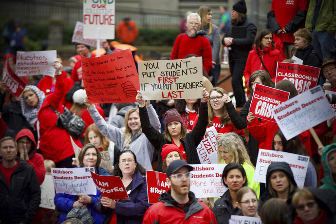 In this April 10, 2019 photo educators from across the metro are gathered at Pioneer Courthouse Square to press the Oregon Legislature for more school funding. Tens of thousands of teachers are expected to walk out across Oregon this week, adding to the string of nationwide protests over class sizes and education funding. Schools around the state, including Oregon's largest district, Portland Public Schools, will close for at least part of Wednesday, May 8, 2019 as educators press for more money from lawmakers. (Mark Graves/The Oregonian via AP)