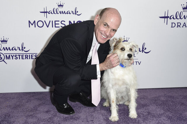 FILE - This July 26, 2018 file photo shows Bill Abbott, left, with a dog named Happy at Hallmark's Evening Gala during the TCA Summer Press Tour in Beverly Hills, Calif. The head of Hallmark's media business is leaving the company after 11 years. No reason was given for Bill Abbott's departure as CEO of Crown Media Family Networks, and no replacement was immediately named.  (Photo by Richard Shotwell/Invision/AP, File)