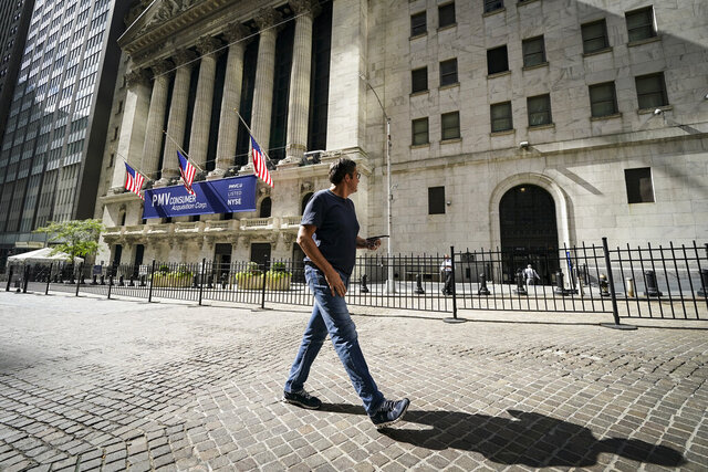 A pedestrian pass the New York Stock Exchange, Friday, Oct. 2, 2020, in New York.  Stocks around the world are falling sharply Wednesday, Oct. 28,  on worries the worsening pandemic will push governments to bring back restrictions on businesses.    (AP Photo/John Minchillo)
