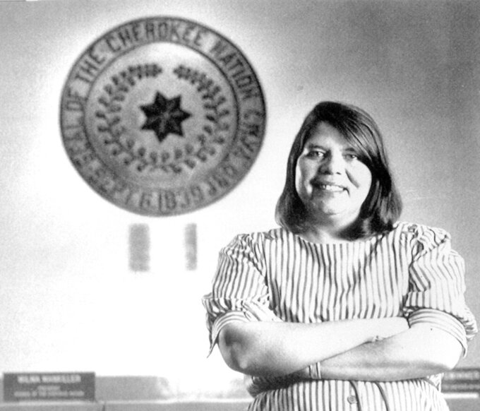FILE - In this July 19, 1985, file photo, Wilma Mankiller, the first woman elected chief of the Cherokee Nation, poses in front of the tribal emblem at the Cherokee Nation in Oklahoma. The U.S. Mint says Mankiller will be among the first five women honored in the new American Women Quarters Program, which starts in 2022 and continues until 2025. (AP Photo, File)