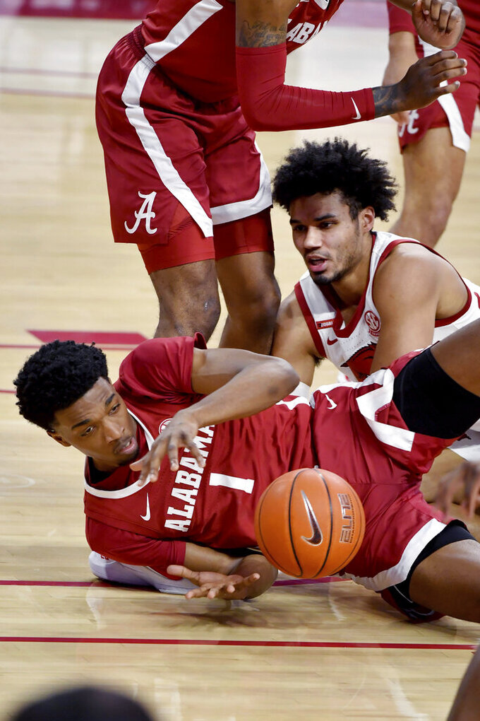 Alabama forward Herbert Jones (1) and Arkansas forward Justin Smith (0) fight for a loose ball during the first half of an NCAA college basketball game in Fayetteville, Ark. Wednesday, Feb. 24, 2021. (AP Photo/Michael Woods)