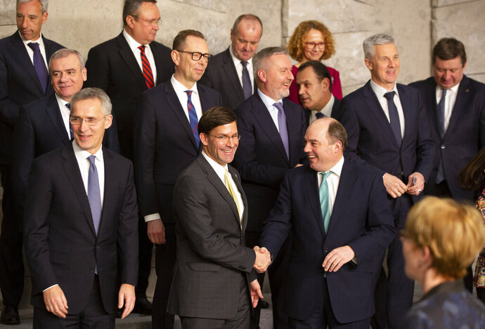 U.S. Secretary for Defense Mark Esper, front center, shakes hands with British Defense Minister Ben Wallace during a group photo of NATO defense ministers at NATO headquarters in Brussels, Wednesday, Feb. 12, 2020. NATO ministers, in a two-day meeting will discuss building stability in the Middle East, the Alliance's support for Afghanistan and challenges posed by Russia's missile systems. (AP Photo/Virginia Mayo)