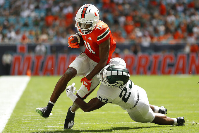 Miami wide receiver Charleston Rambo (11) breaks a tackle from Michigan State safety Darius Snow (23) during the second quarter of an NCAA college football game, Saturday, Sept. 18, 2021, in Miami Gardens, Fla. (AP Photo/Michael Reaves)