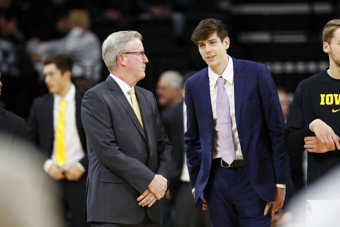 Iowa head coach Fran McCaffery, left, talks with his son forward Patrick McCaffery, right, before an NCAA college basketball game against Oral Roberts, Friday, Nov. 15, 2019, in Iowa City, Iowa. (AP Photo/Charlie Neibergall)
