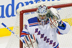 New York Rangers goaltender Igor Shesterkin (31) makes a save high in the net during the third period of an NHL hockey game against the New Jersey Devils, Tuesday, April 13, 2021, in Newark, N.J. The Rangers shut out the Devils 3-0. (AP Photo/Kathy Willens)