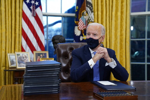 FILE - In this Jan. 20, 2021, file photo President Joe Biden waits to sign his first executive order in the Oval Office of the White House in Washington. As one of his first acts, Biden offered a sweeping immigration overhaul that would provide a path to U.S. citizenship for the estimated 11 million people who are in the United States illegally. It would also codify provisions wiping out some of President Donald Trump's signature hard-line policies, including trying to end existing, protected legal status for many immigrants brought to the U.S. as children and crackdowns on asylum rules.(AP Photo/Evan Vucci, File)