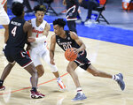 South Carolina guard AJ Lawson (00) dribbles around Florida guard Tre Mann (1) during the first half of an NCAA college basketball game Wednesday, Feb. 3, 2021, in Gainesville, Fla. (AP Photo/Matt Stamey)