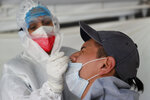 A health worker collects a nasal swab sample for a COVID-19 test in Mexico City, Monday, Aug. 9, 2021. (AP Photo/Marco Ugarte)