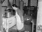 FILE - In this April 1938, file photo, Mrs. G.S. Davis, wife of a Corinth, Miss., farmer, works in her electrified kitchen in their farm home somewhere in Tenn. The wood burning stove hasn't yet been removed. Mr. Davis has numerous electrical conveniences installed in the farm, among them a potato drier, electric pump, electric charged fence constructed around the yard. California's energy policy and planning agency wants to transition new homes away from gas-powered appliances. The California Energy Commission released a draft building standards code on Thursday, May 6, 2021, that would require new homes to be equipped with circuits and panels that support all-electric appliances for heating, cooking and drying clothes. (AP Photo/Horace Cort, File)