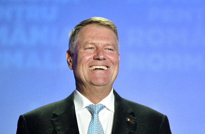 Romanian President Klaus Iohannis smiles upon seeing exit polls results which indicate him as the leader of the presidential race, with up to 40 percent of the votes in Bucharest, Romania, Sunday, Nov. 10, 2019.  Romania held a presidential election Sunday after a lackluster campaign that has been overshadowed by the country's political crisis, which saw a minority government installed just a few days ago. (AP Photo/Andreea Alexandru)