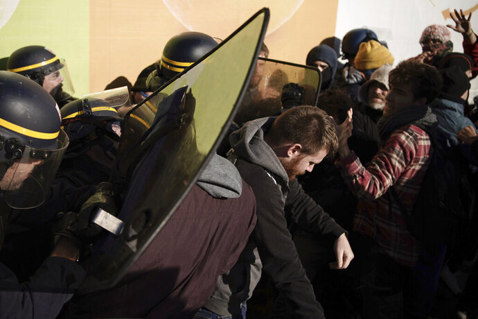French police officers push back pro-Catalan independence demonstrators as they try to block a major highway border pass near La Jonquera between Spain and France, Monday, Nov. 11, 2019. Protesters following a call to action by a secretive pro-Catalan independence group have closed off both sides of the AP7 highway at the major transportation hub of La Jonquera between France and Spain. (AP Photo/Felipe Dana)