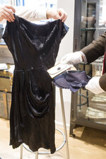 """Empolyees hold a cocktail dress, a wallet and a strawhat that belonged to Eva Braun the wife of Adolf Hitler prior to an auction in Grasbrunn, Germany, Wednesday, Nov. 20, 2019. A Jewish group has sharply condemned an auction of Nazi memorabilia in Germany. The European Jewish Association condemned the auction Wednesday at Hermann Historica in Munich, saying that """"it's wrong to make money off these blood-soaked items, especially in Germany of all places"""