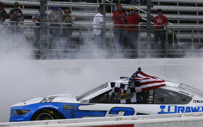 \Brad Keselowski does a burnout while holding a flag after winning the NASCAR Cup Series auto race at Martinsville Speedway in Martinsville, Va., Sunday, March 24, 2019. (AP Photo/Steve Helber)
