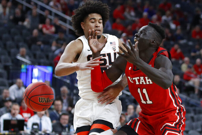 Oregon State's Ethan Thompson (5) steals the ball from Utah's Both Gach (11) during the second half of an NCAA college basketball game in the first round of the Pac-12 men's tournament Wednesday, March 11, 2020, in Las Vegas. (AP Photo/John Locher)