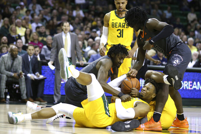 Baylor forward Freddie Gillespie, center, grabs a rebound between Oklahoma State forward Kalib Boone, left, and guard Isaac Likekele, right, during the first half of an NCAA college basketball game Saturday, Feb. 8, 2020, in Waco, Texas. (AP Photo/Rod Aydelotte)