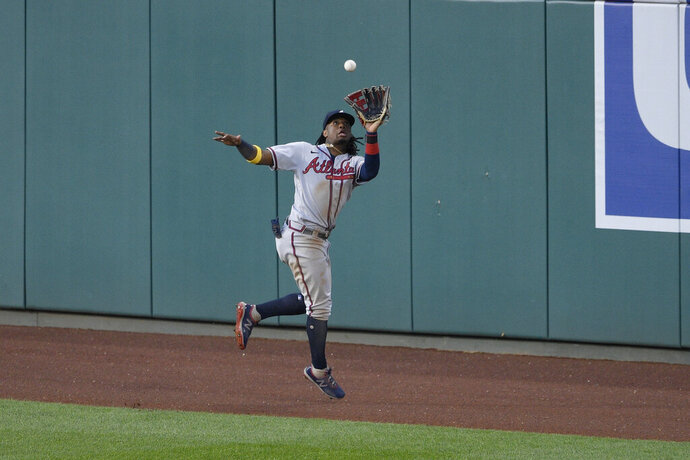 Atlanta Braves center fielder Ronald Acuna Jr. jumps and makes the catch on a line drive by Washington Nationals' Trea Turner during the third inning of a baseball game Saturday, Sept. 12, 2020, in Washington. (AP Photo/Nick Wass)