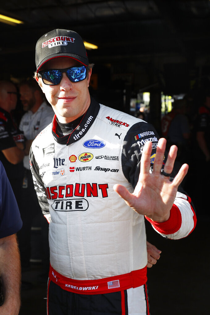 Brad Keselowski waves after winning the pole during qualifying for the NASCAR Cup Series auto race at Michigan International Speedway in Brooklyn, Mich., Friday, Aug. 9, 2019. (AP Photo/Paul Sancya)