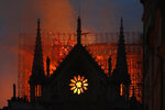 FILE - Flames and smoke rise from Notre Dame cathedral as it burns in Paris, Monday, April 15, 2019. The city of Paris has ordered a deep cleaning of schools nearest Notre Dame, whose lead roof melted away in the fire last April. (AP Photo/Thibault Camus, File)