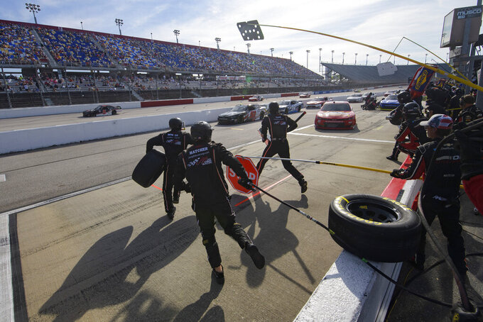 Tyler Reddick pits as crew members jump into action during a NASCAR Xfinity Series auto race Saturday, Sept. 4, 2021, in Darlington, S.C. (AP Photo/John Amis)