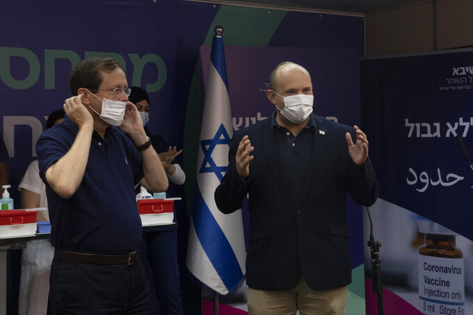 Israeli President Isaac Herzog left, puts on his mask as Prime Minister Naftali Bennett, right, speaks to journalists after Herzog received a third coronavirus vaccine at Sheba Medical Center in Ramat Gan, Israel, Friday, July 30, 2021. (AP Photo/Maya Alleruzzo, Pool)