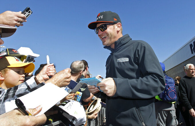 Driver Clint Bowyer signs autographs for fans prior to the start of the NASCAR Cup Series auto race at ISM Raceway, Sunday, March 10, 2019, in Avondale, Ariz. (AP Photo/Ralph Freso)