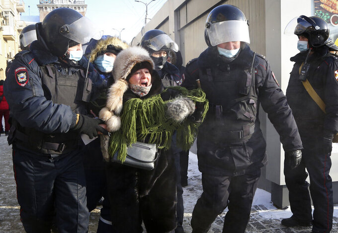 Police detain a woman during a protest against the jailing of opposition leader Alexei Navalny in Siberian city of Omsk, Russia, Saturday, Jan. 23, 2021. Russian police on Saturday arrested hundreds of protesters who took to the streets in temperatures as low as minus-50 C (minus-58 F) to demand the release of Alexei Navalny, the country's top opposition figure.  Navalny, President Vladimir Putin's most prominent foe, was arrested on Jan. 17 when he returned to Moscow from Germany, where he had spent five months recovering from a severe nerve-agent poisoning that he blames on the Kremlin. (AP Photo)