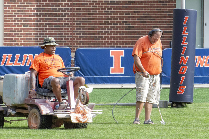University of Illinois athletic facility attendants Tyrone Washington, left, and Shawn Hannan, right, renew the line markers of the schools football practice field in Champaign, Ill., Wednesday, Sept. 16, 2020. Less than five weeks after pushing fall sports to spring in the name of player safety during the pandemic, the Big Ten conference changed course Wednesday and said it plans to open its football season the weekend of Oct. 23-24. (Robin Scholz/The News-Gazette via AP)