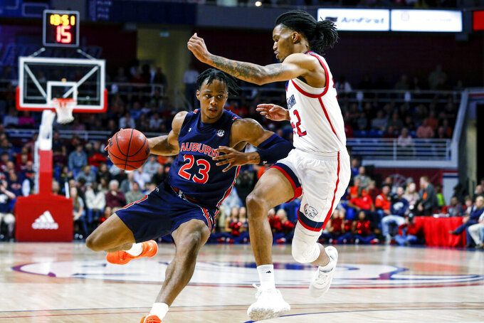 Auburn forward Isaac Okoro (23) drives to the basket as South Alabama forward Trhae Mitchell (42) defends during the second half of an NCAA college basketball game, Tuesday, Nov. 12, 2019, in Mobile, Ala. Auburn won 70-69. (AP Photo/Butch Dill)