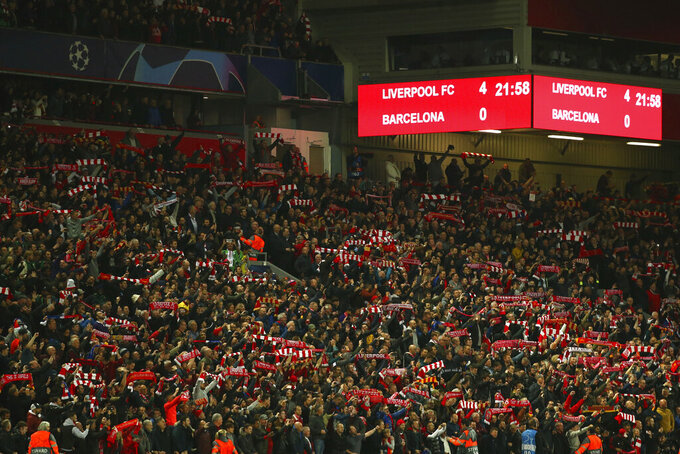 FILE - In this May 7, 2019, file photo, Liverpool supporters celebrate after winning the Champions League semifinal, second leg, soccer match 4-0 against FC Barcelona at the Anfield stadium in Liverpool, England. (AP Photo/Dave Thompson, File)