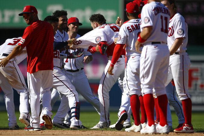 Washington Nationals' Carter Kieboom, center, is mobbed by teammates after he hit a walkoff single to drive in Josh Bell during the ninth inning of a baseball game against the New York Mets, Monday, Sept. 6, 2021, in Washington. (AP Photo/Nick Wass)